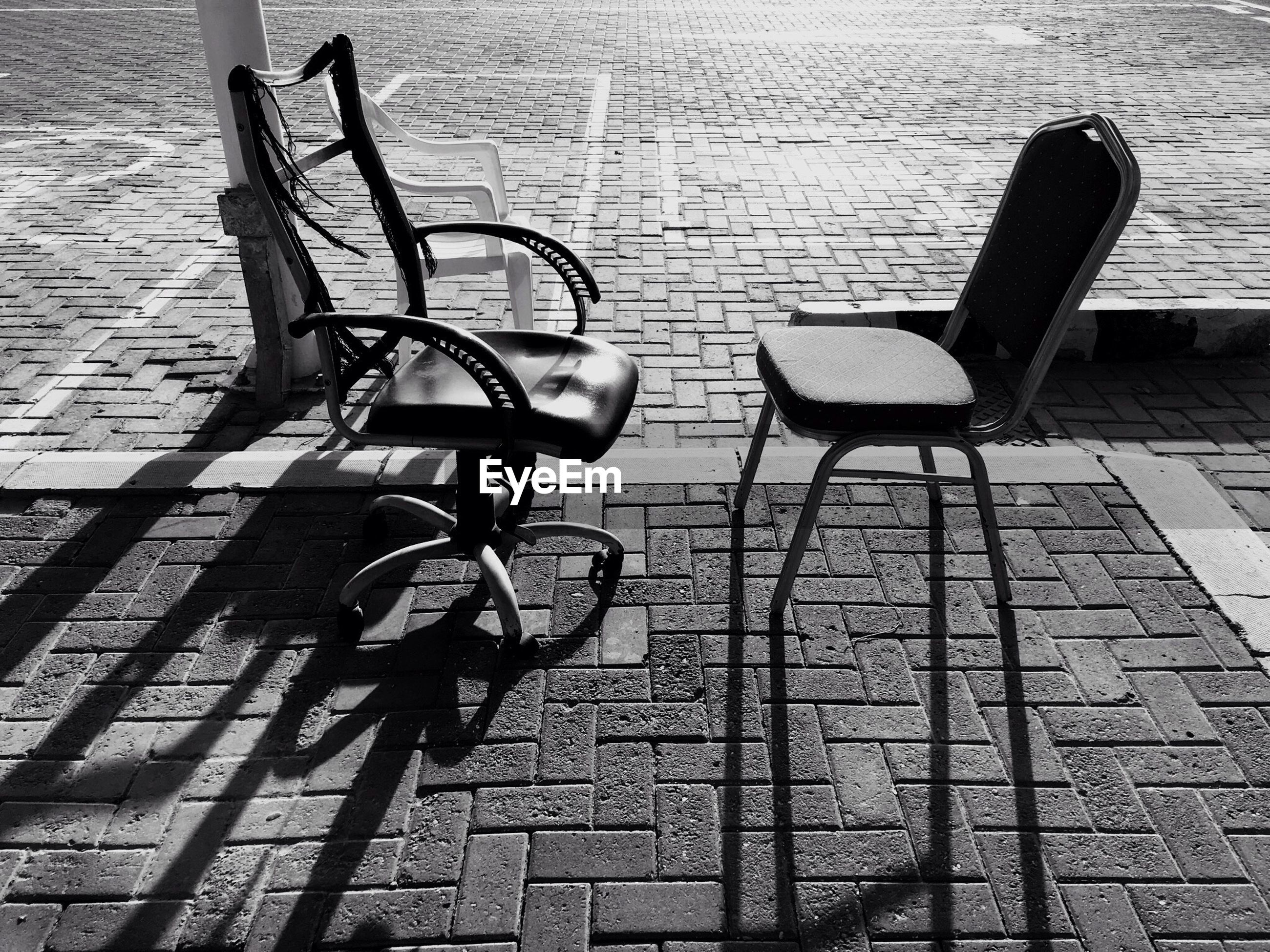 Side view of empty chairs on cobblestone