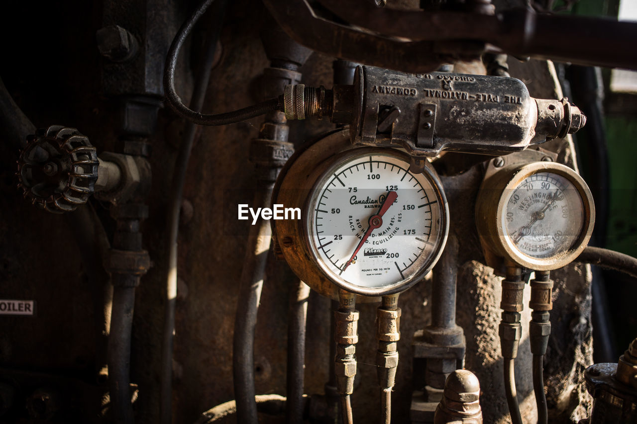 CLOSE-UP OF OLD CLOCK ON METAL MACHINE