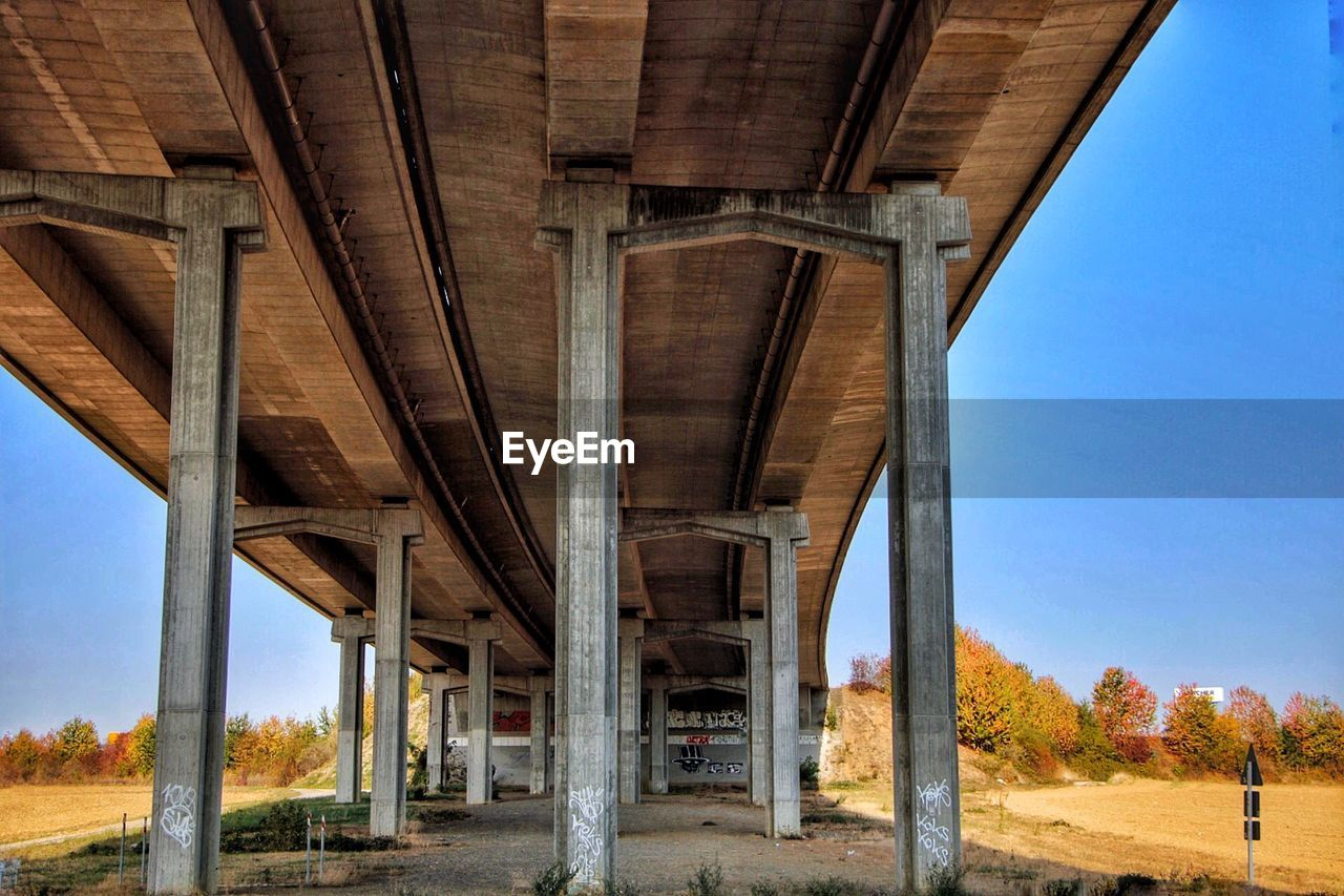 architecture, bridge, architectural column, built structure, bridge - man made structure, nature, no people, transportation, day, connection, road, sky, low angle view, clear sky, below, outdoors, tree, highway, land, underneath, girder, overpass