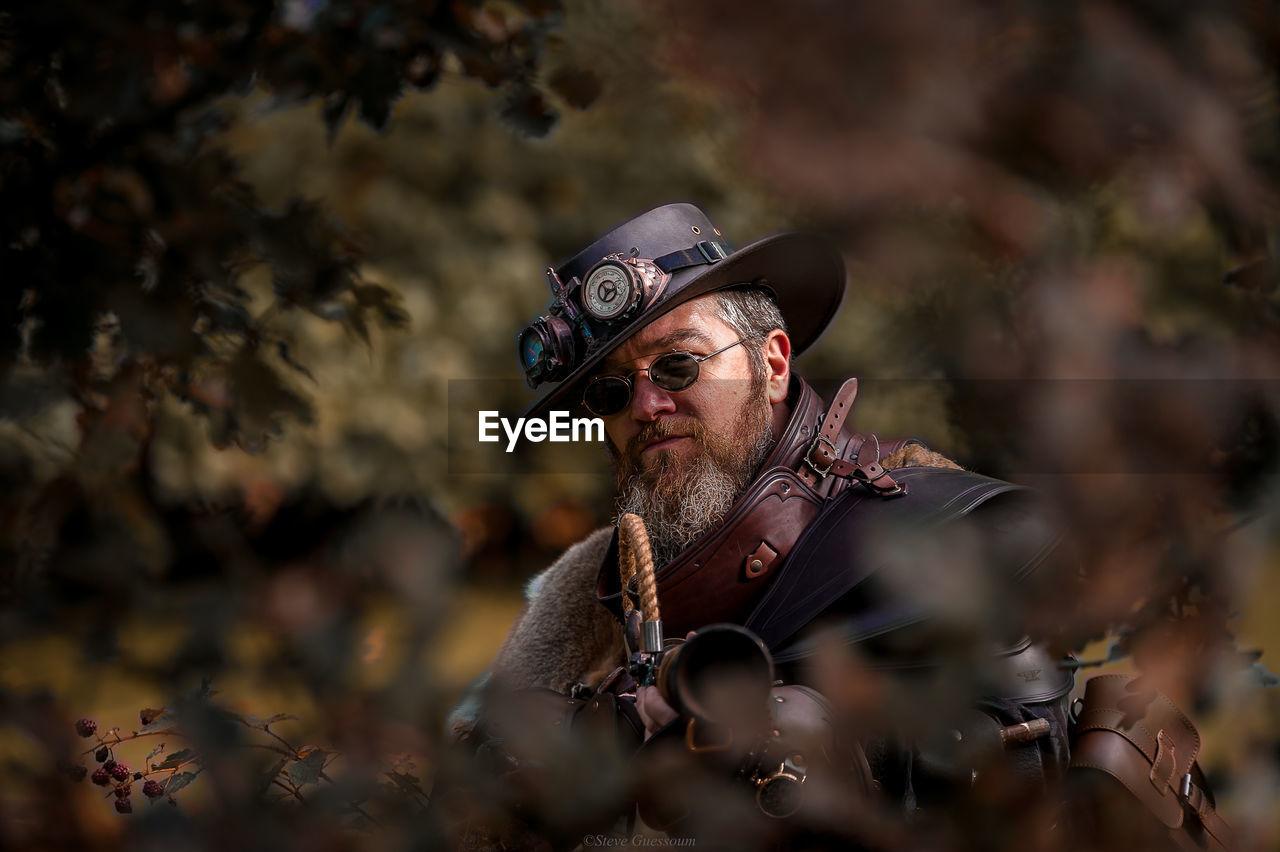 Portrait of man wearing hat aiming gun