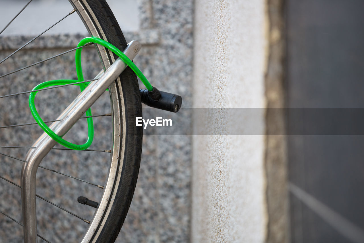 Close-Up Of Green Lock On Bicycle Tire At Rack