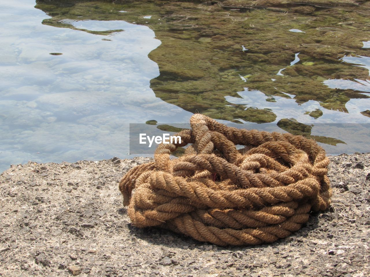 water, nature, day, no people, high angle view, lake, close-up, outdoors, reflection, beach, beauty in nature, tranquility, solid, stack, rope, rock, sunlight, focus on foreground, strength, tangled