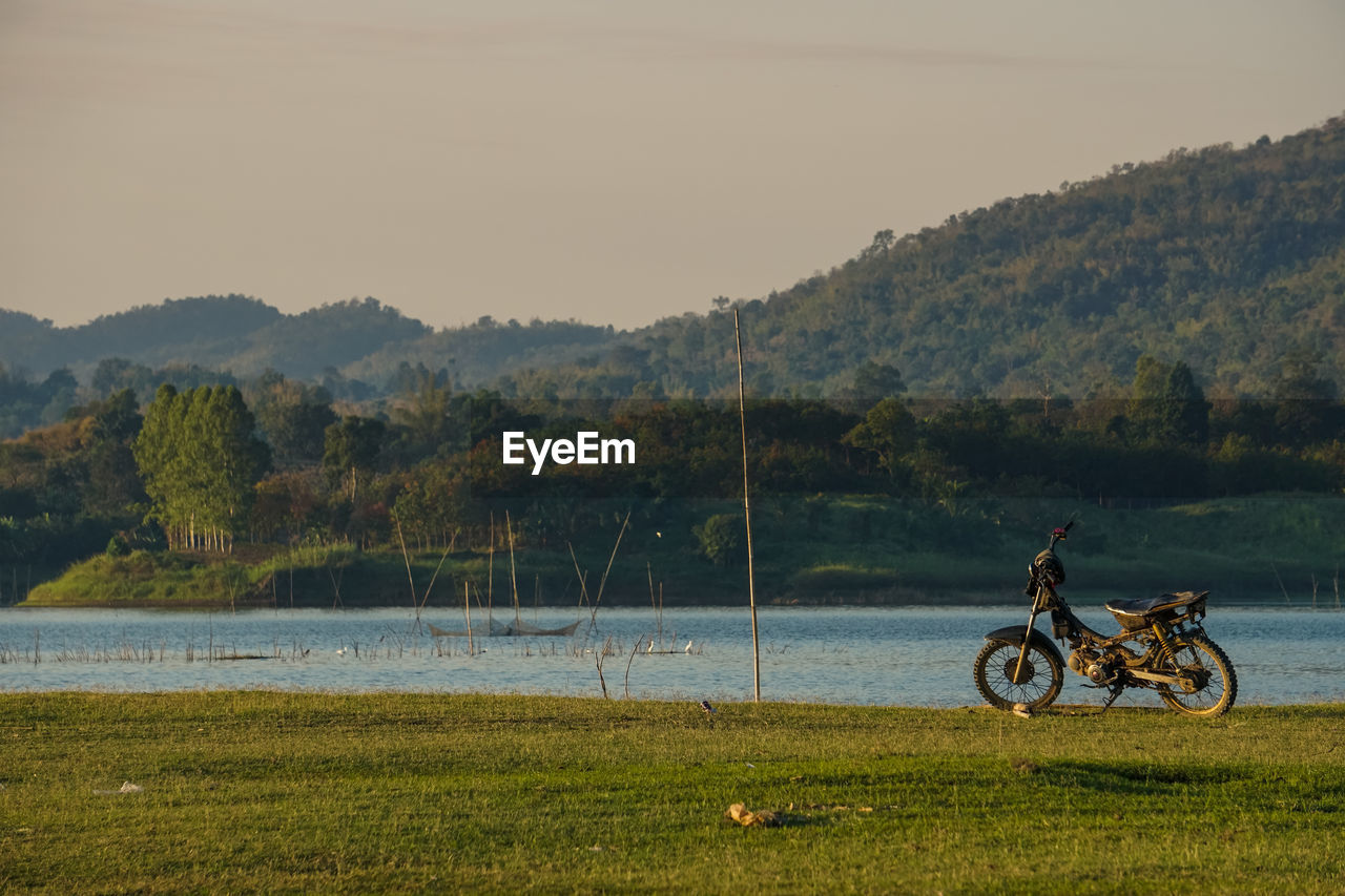 water, transportation, plant, sky, mode of transportation, lake, nature, grass, bicycle, land vehicle, scenics - nature, beauty in nature, day, tree, mountain, field, tranquility, non-urban scene, lifestyles, outdoors, riding