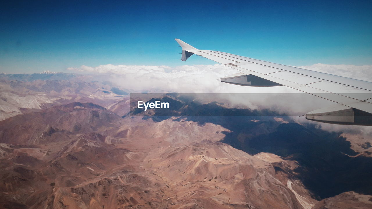 AERIAL VIEW OF AIRPLANE FLYING OVER MOUNTAINS