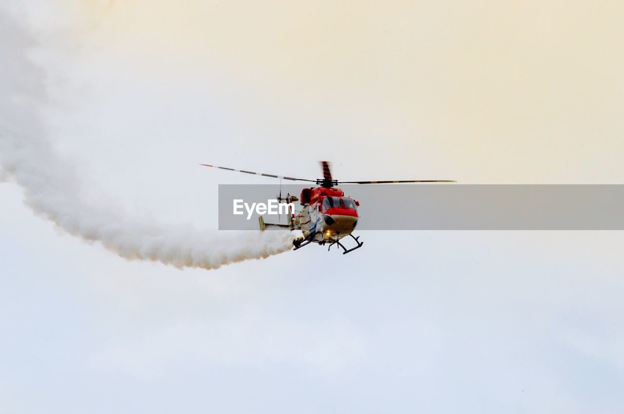 Low Angle View Of Smoke Emitting From Helicopter Against Sky