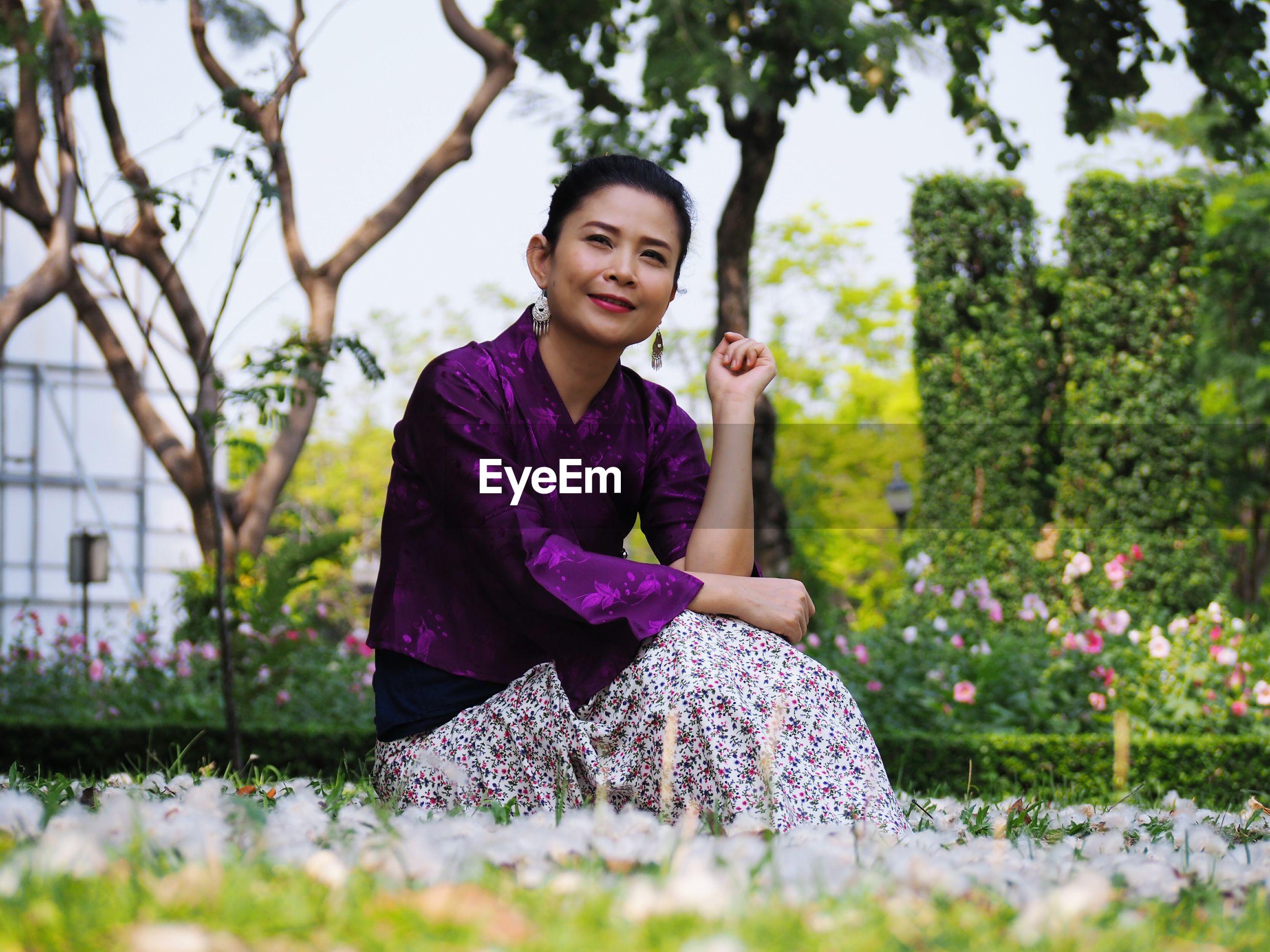 Thoughtful mature woman sitting on field