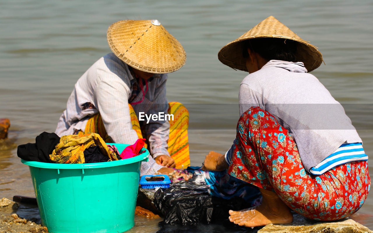 Women Cleaning Clothes At Riverbank