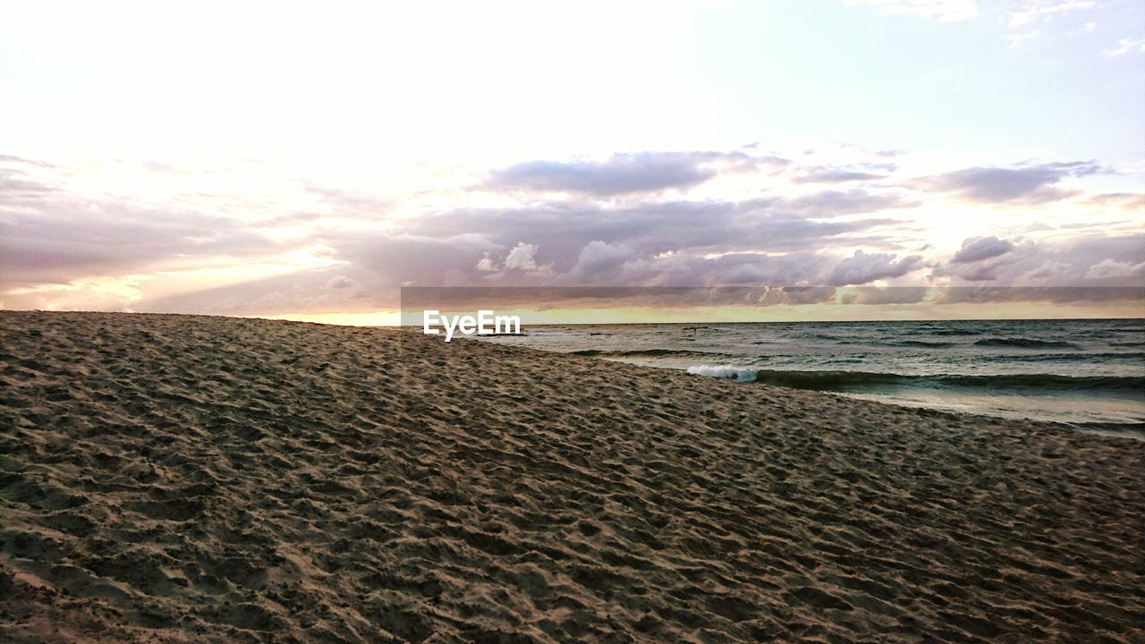 Scenic View Of Sandy Beach Against Sky During Sunset