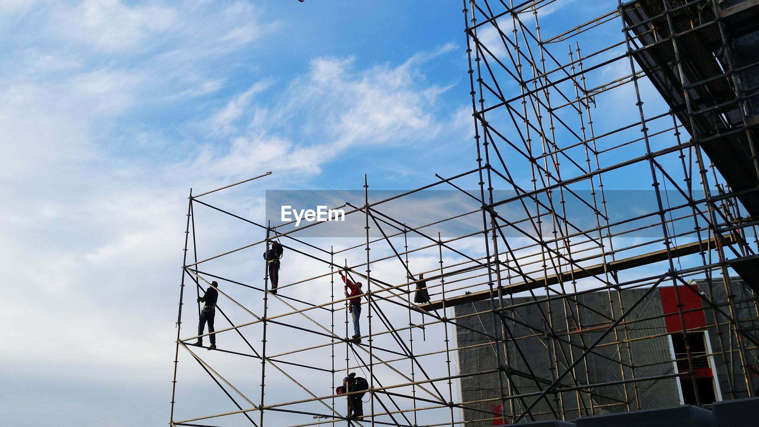 Low angle view of manual workers on scaffoldings against sky