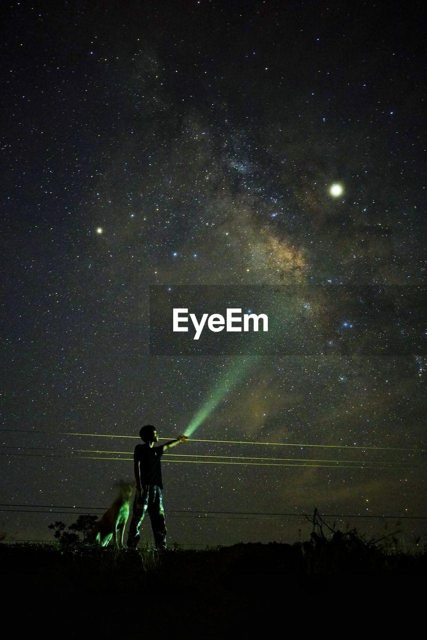 Man holding illuminated flashlight while standing on land against sky at night