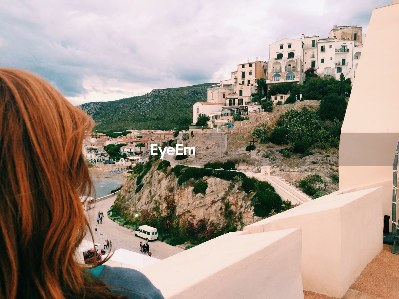 Rear view of woman watching town on coastline