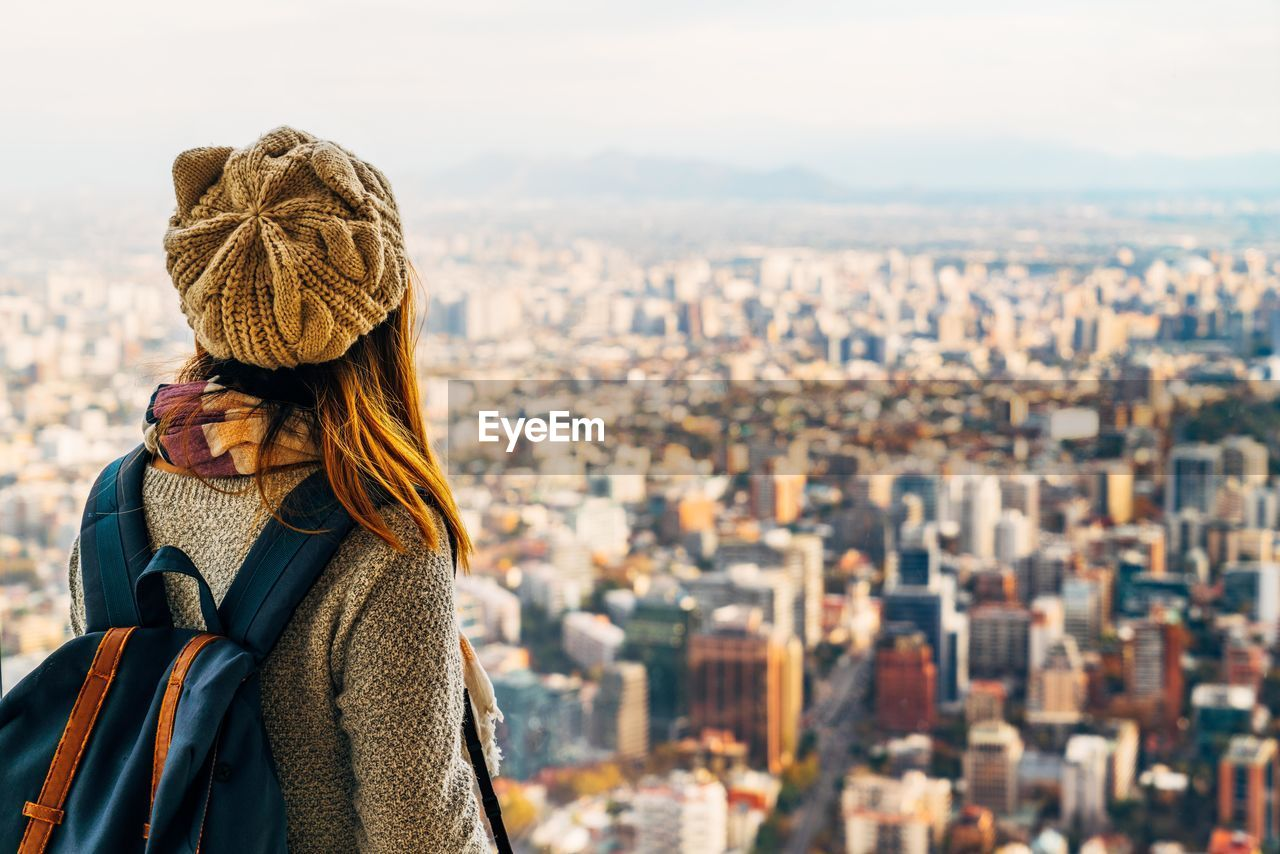 Rear View Of Young Woman With Backpack Standing Against Cityscape