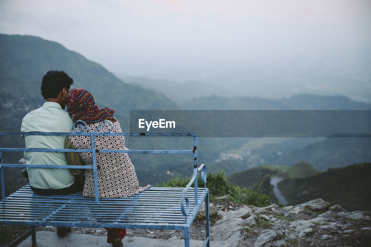 Rear View Of Couple Sitting On Seat Against Mountains