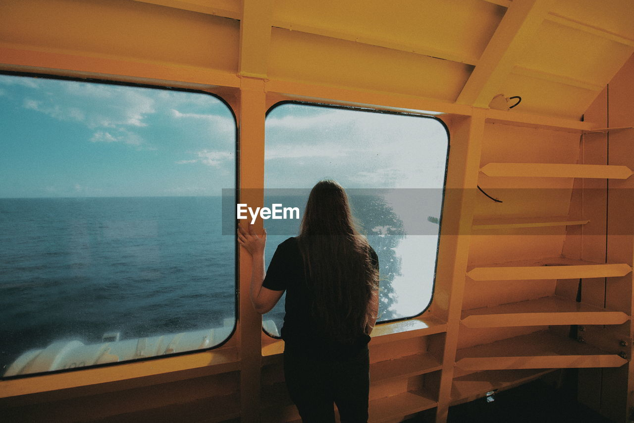 Rear View Of Woman Looking Through Boat Window