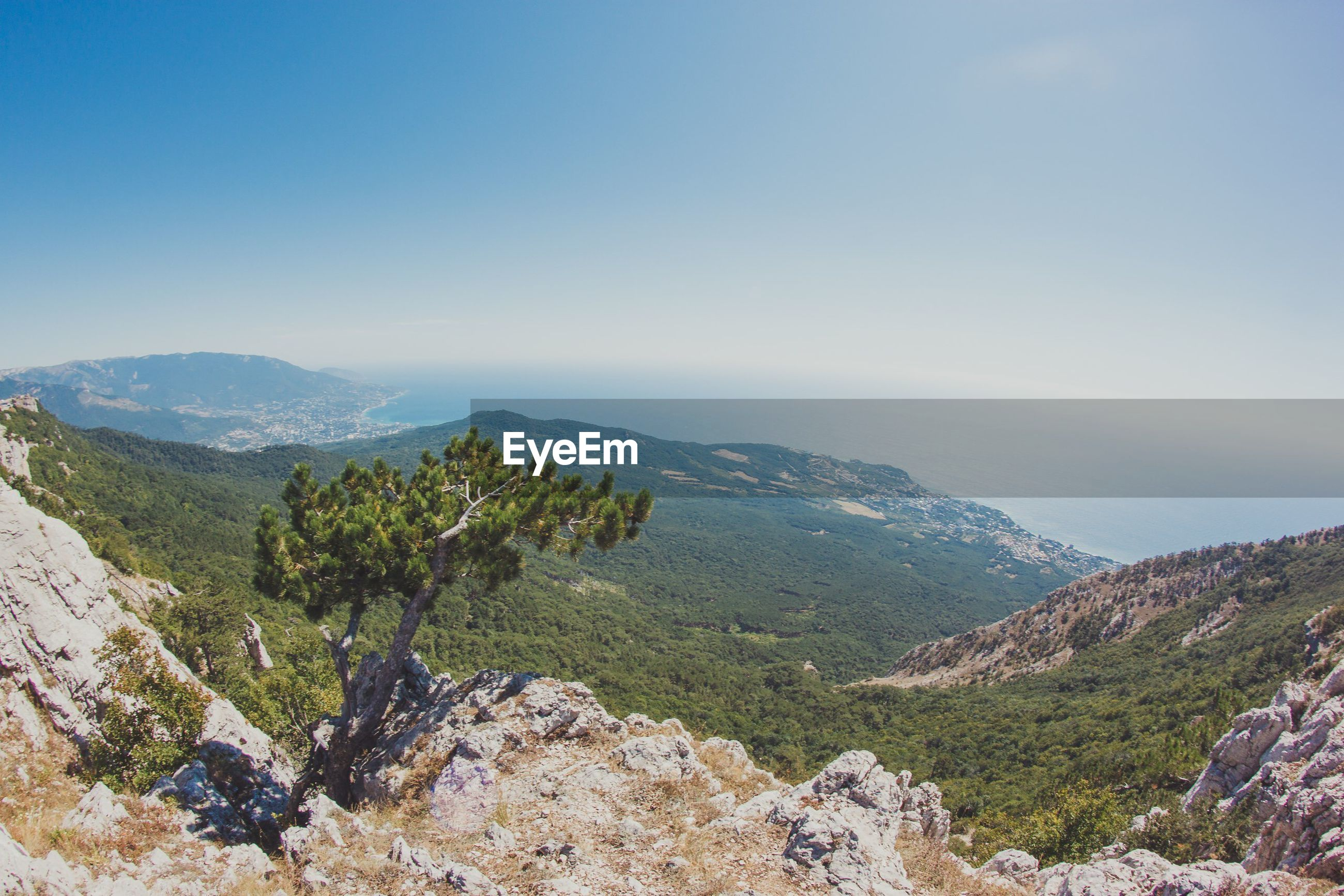 Scenic view of mountains and sea against clear sky
