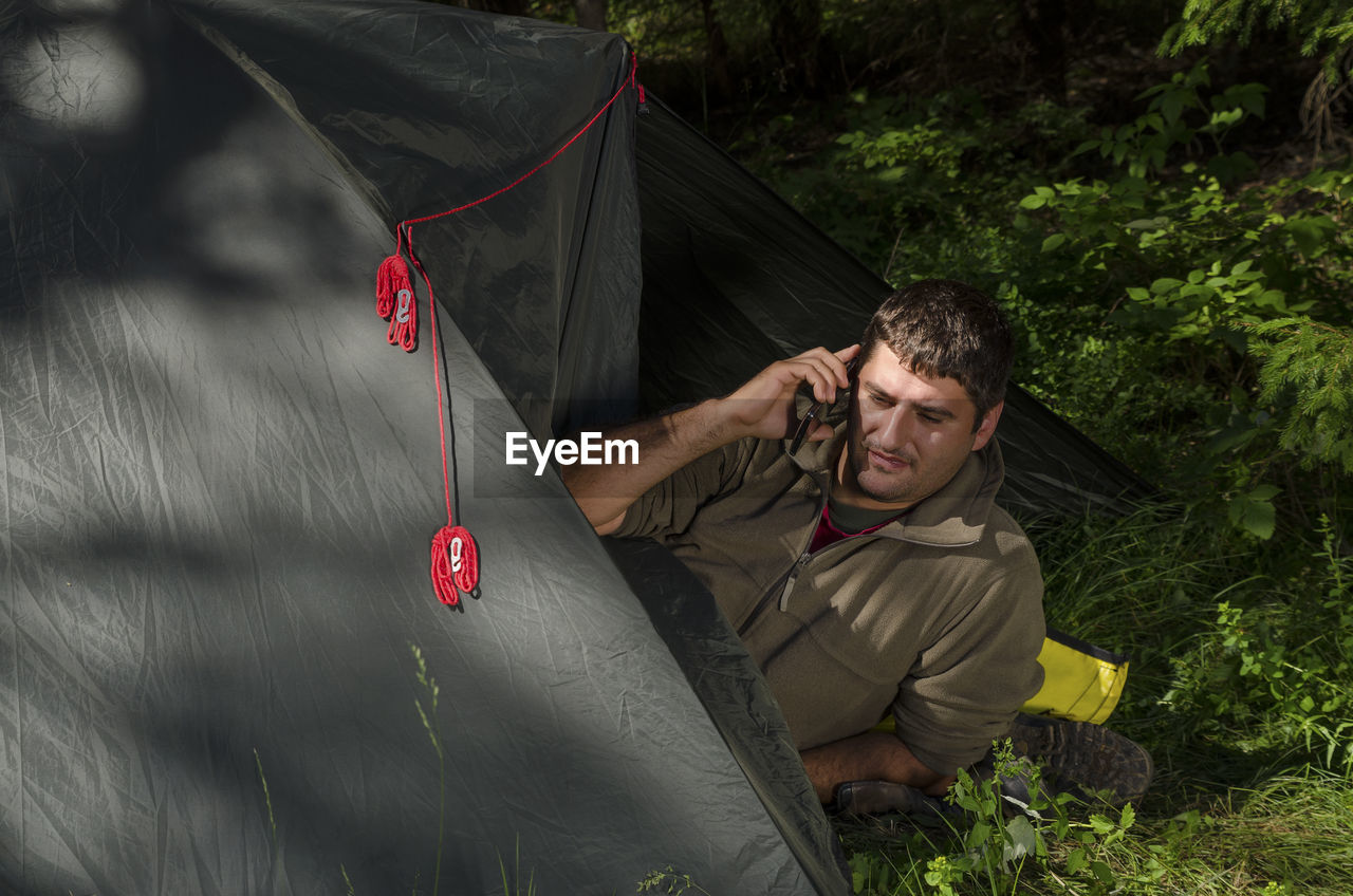 High angle view of man talking on phone while resting in tent at campsite