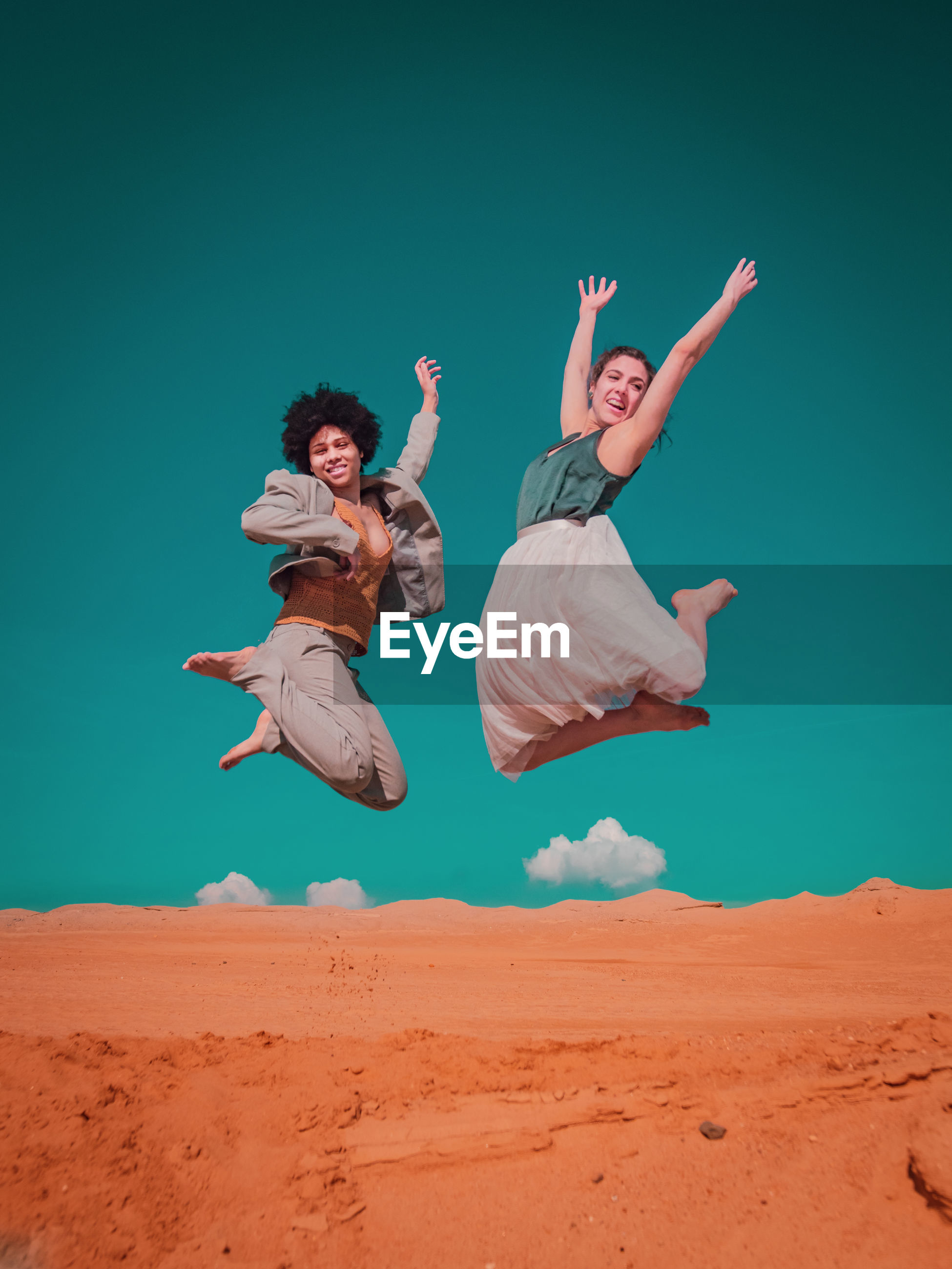 Lesbian couple jumping over sand against clear blue sky