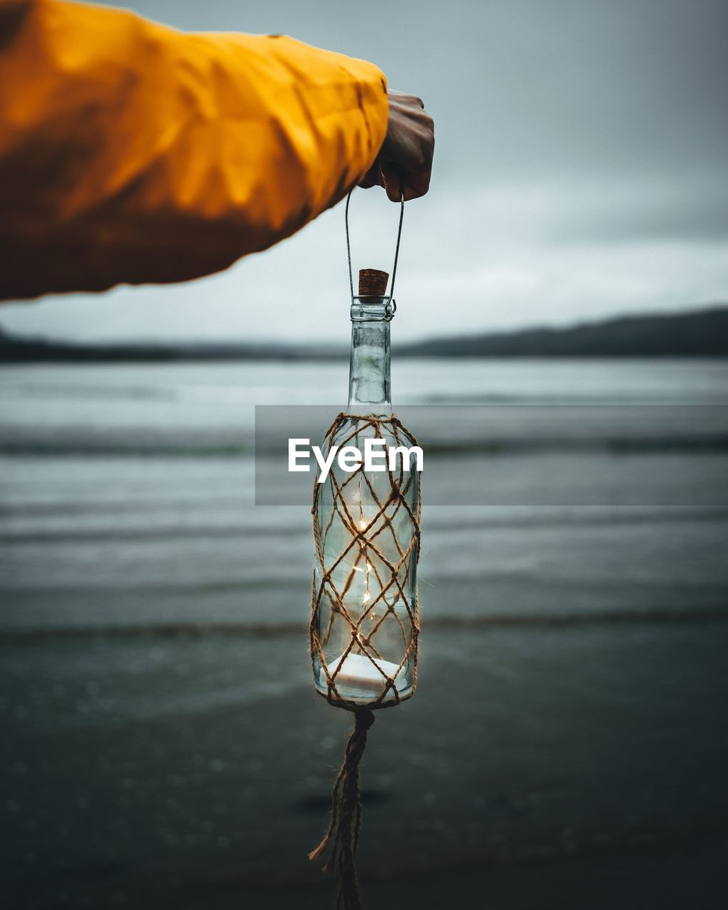 Close-up of hand holding illuminated bottle at beach