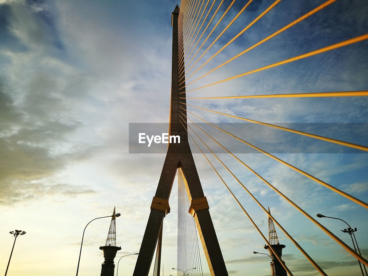 sky, cloud - sky, low angle view, built structure, architecture, no people, bridge - man made structure, bridge, nature, connection, transportation, outdoors, day, sunset, tall - high, cable-stayed bridge, travel destinations, street light, tourism