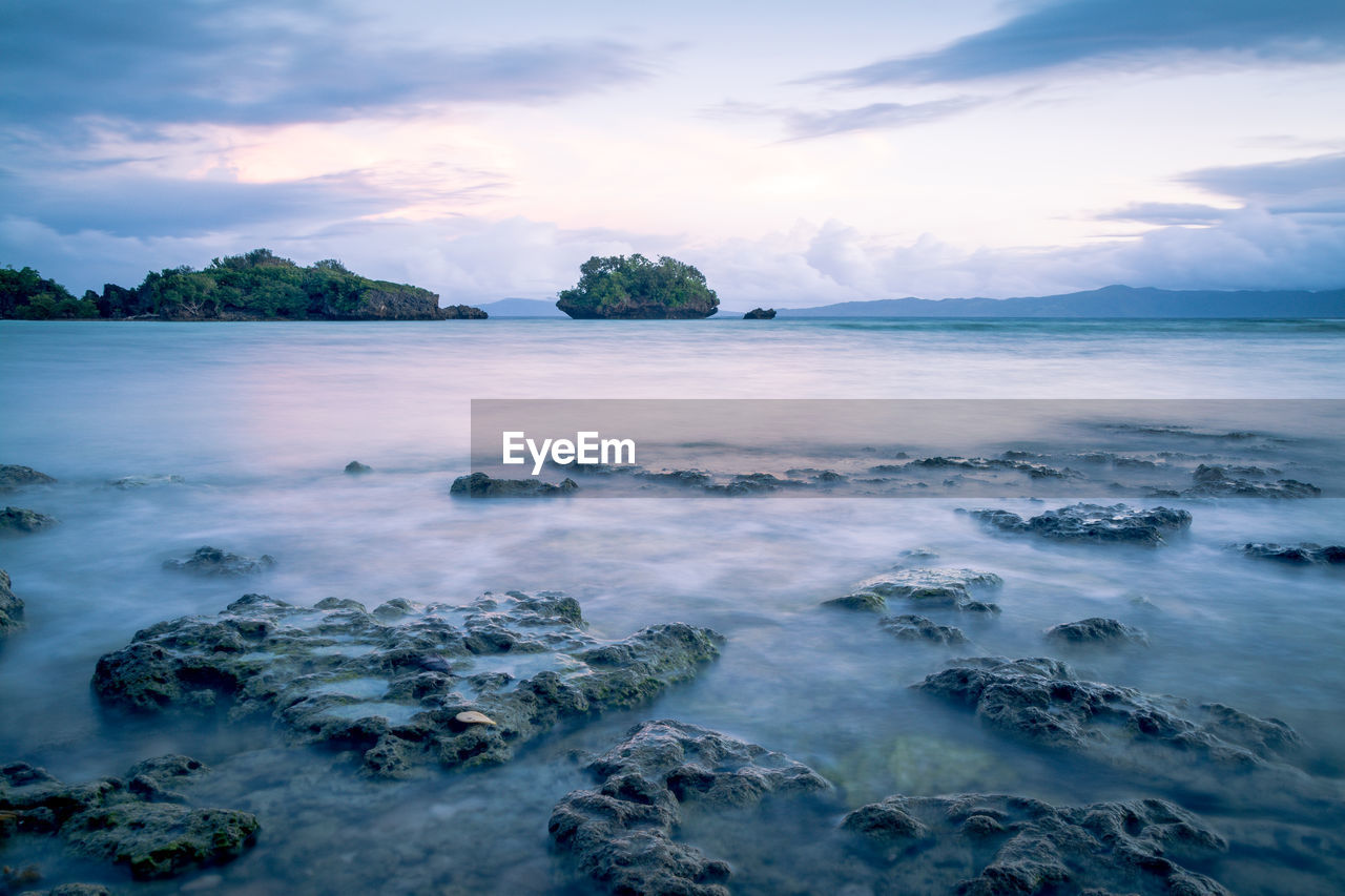 View Of Rocks In Water At Lake Against Cloudy Sky