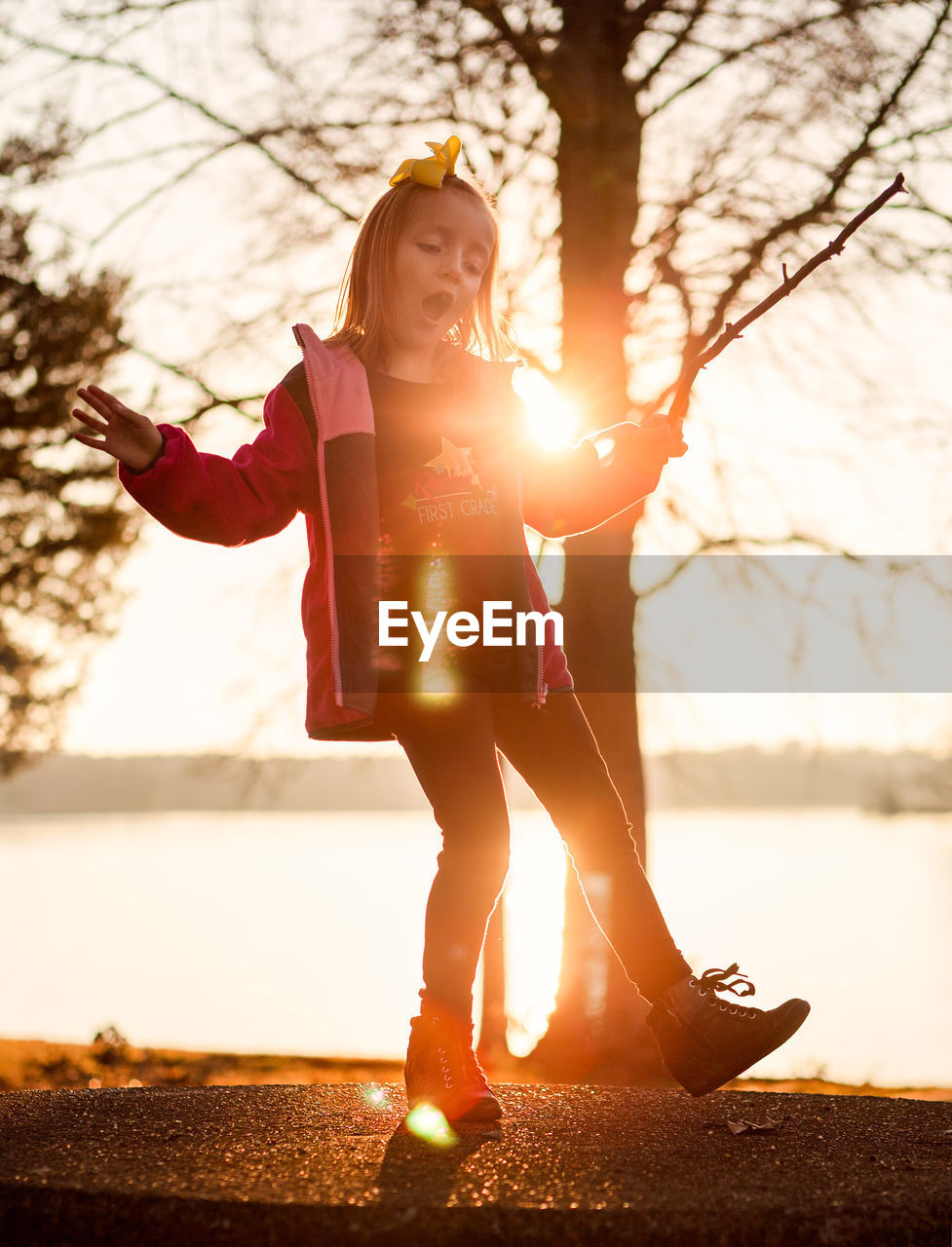 Full length of girl standing by lake against sky during sunset