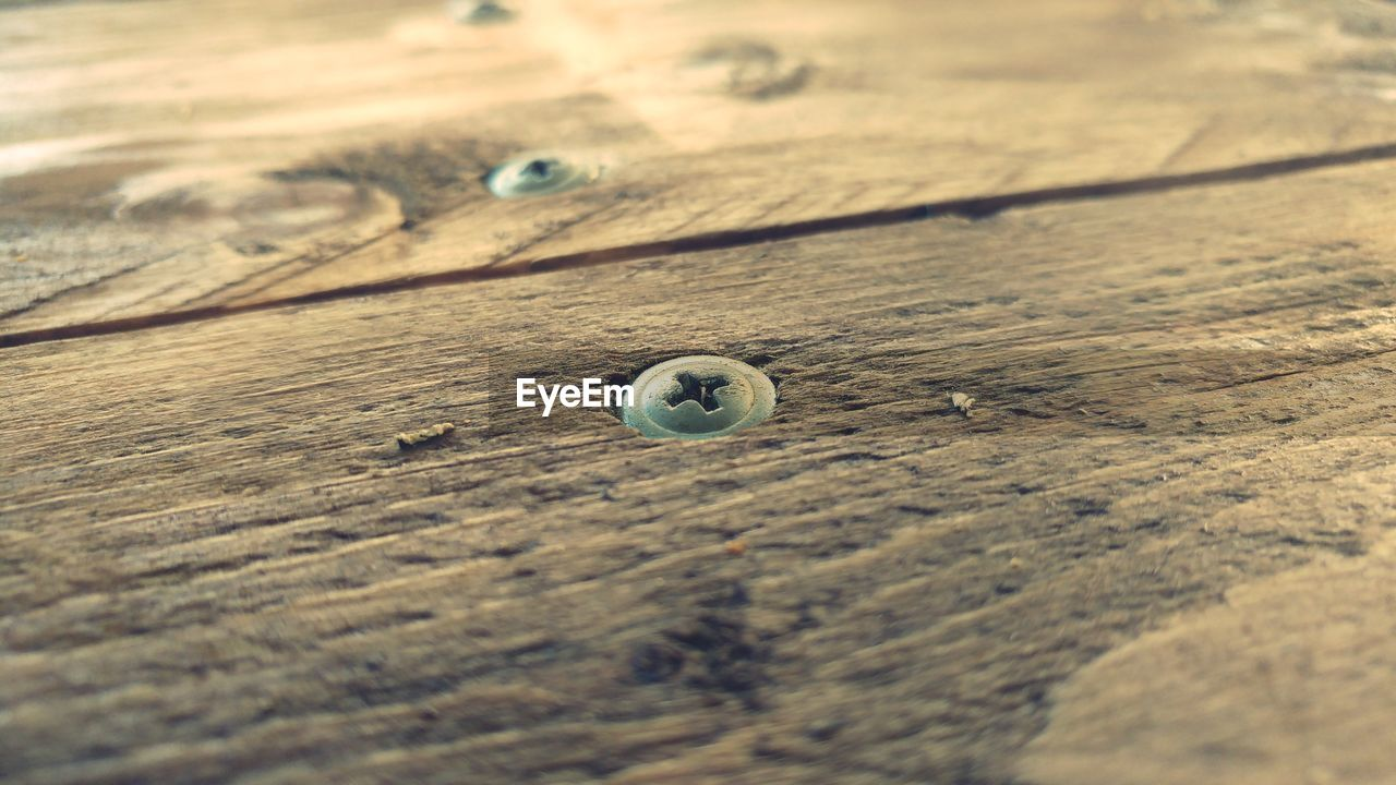 wood - material, selective focus, close-up, no people, day, textured, button, nature, wood, table, pattern, still life, high angle view, outdoors, backgrounds, shape, sand, circle, full frame, wood grain