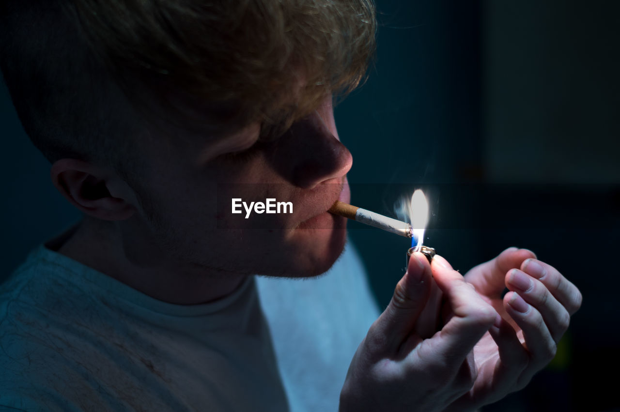 Close-Up Of Man Lighting Cigarette