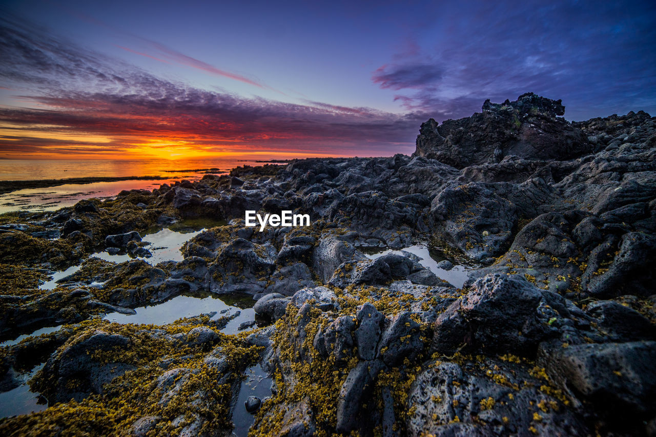 Scenic view of rocks at beach against sky during sunset