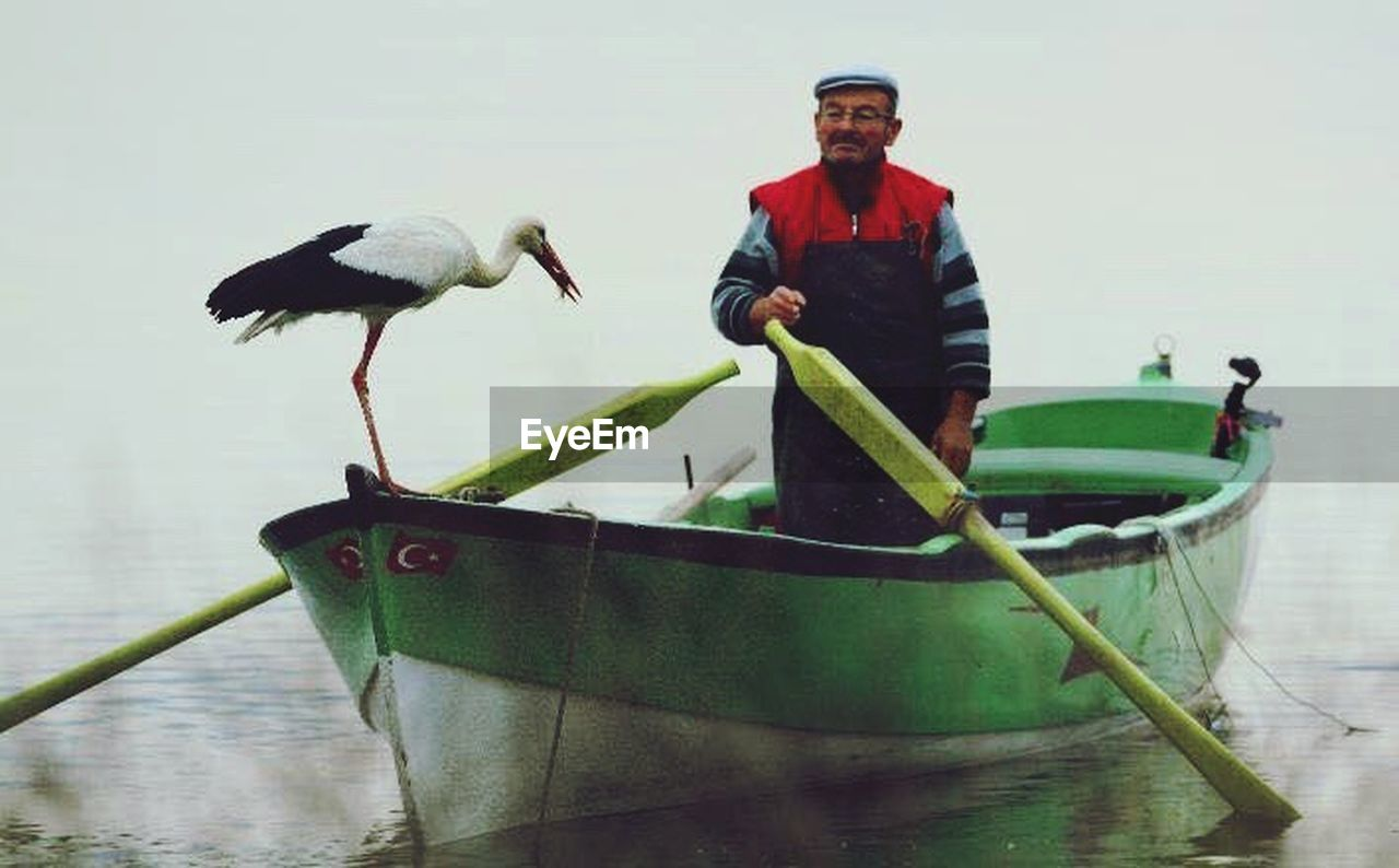 nautical vessel, one person, real people, mature adult, looking at camera, outdoors, standing, bird, portrait, day, occupation, adult, full length, men, water, one man only, nature, oar, people, adults only, only men