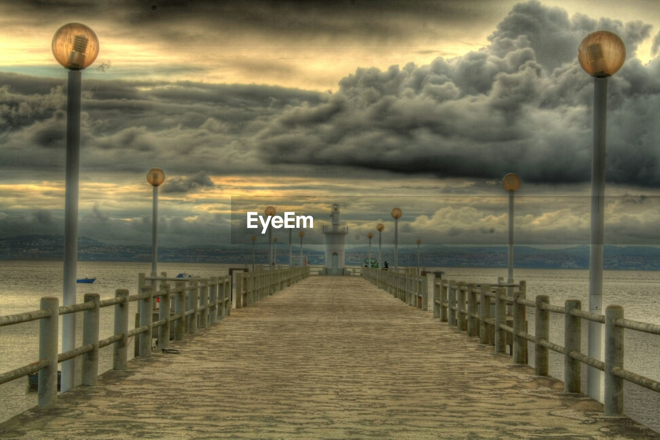 Pier over sea against dramatic sky