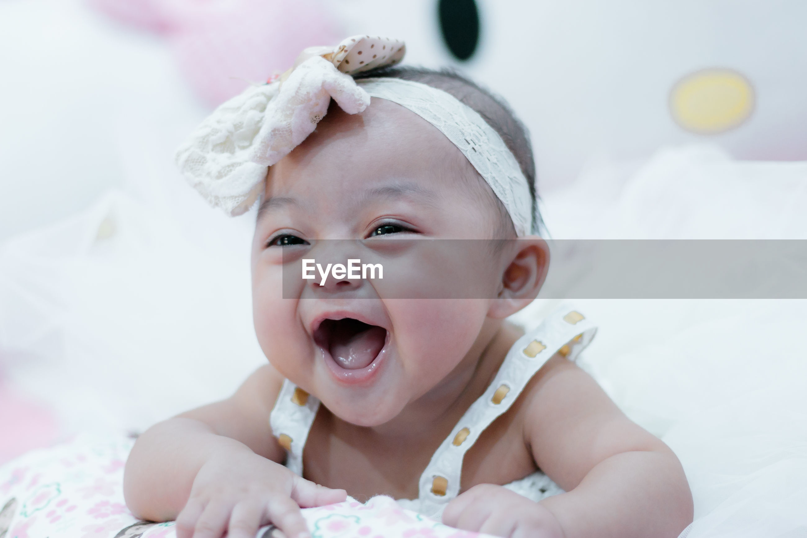 Close-up of cute baby girl on bed