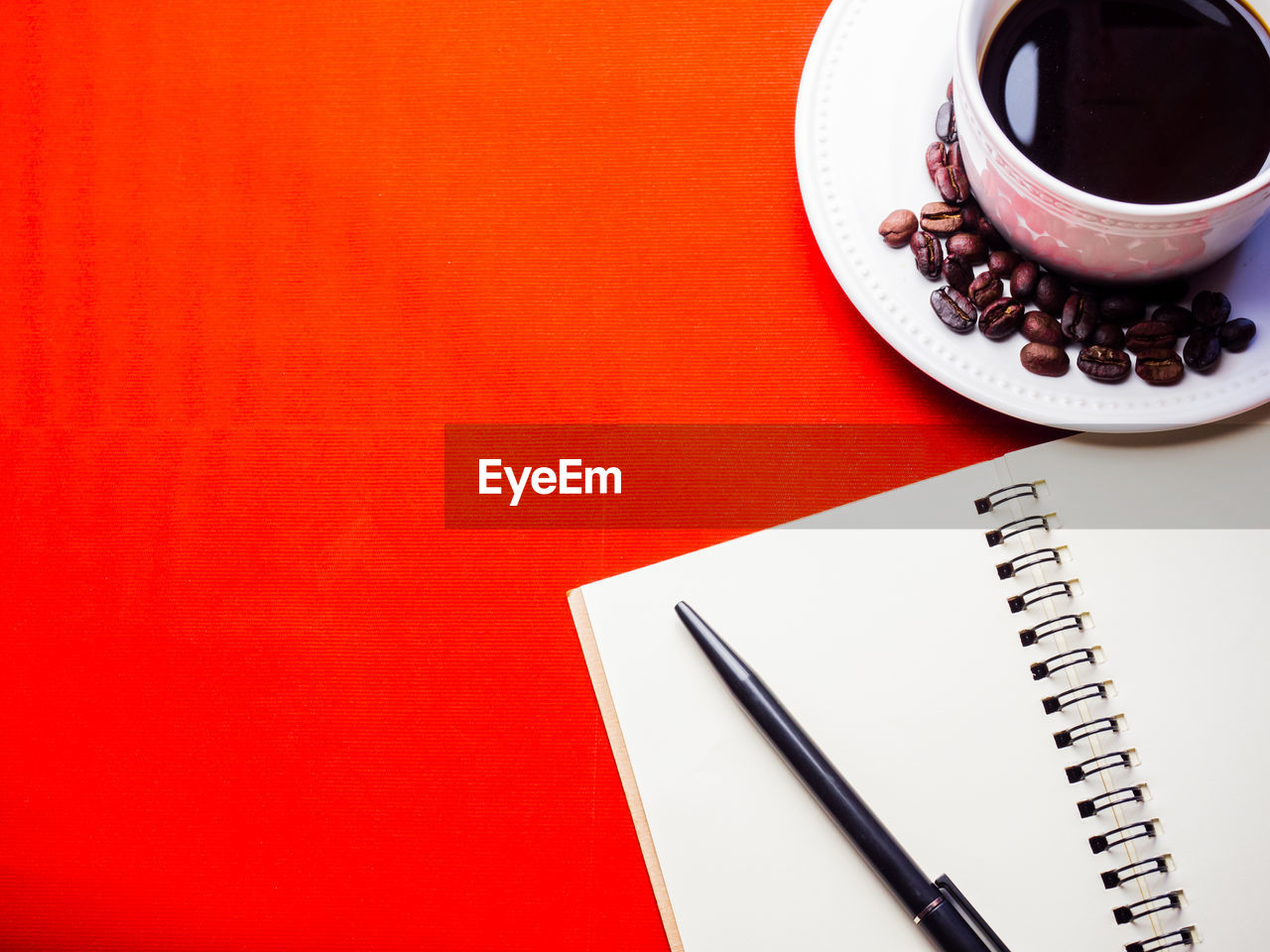 cup, table, still life, pen, copy space, drink, mug, high angle view, coffee - drink, indoors, food and drink, coffee cup, coffee, no people, refreshment, note pad, spiral notebook, studio shot, red, publication, blank, crockery