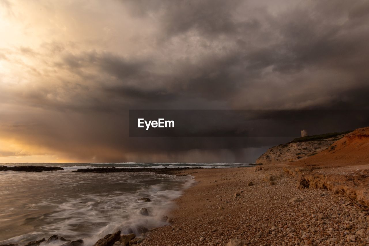 cloud - sky, sky, sea, beauty in nature, water, beach, scenics - nature, storm, land, horizon over water, overcast, horizon, storm cloud, no people, nature, motion, sunset, power in nature, outdoors, ominous