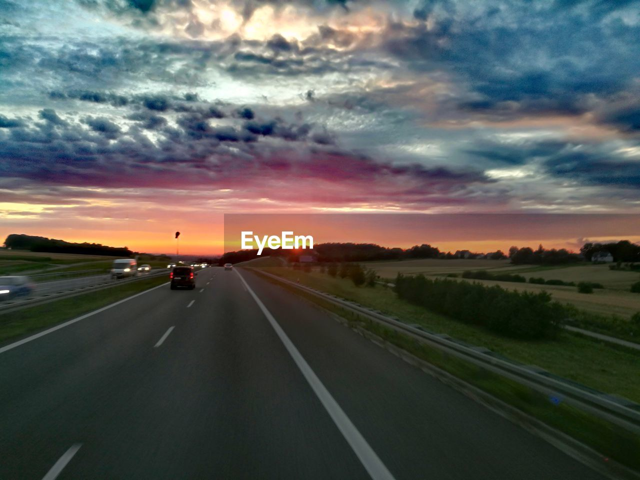 sunset, road, cloud - sky, transportation, sky, the way forward, road marking, dramatic sky, car, travel, land vehicle, sun, mode of transport, scenics, nature, no people, dividing line, outdoors, car point of view, landscape, beauty in nature, storm cloud, day