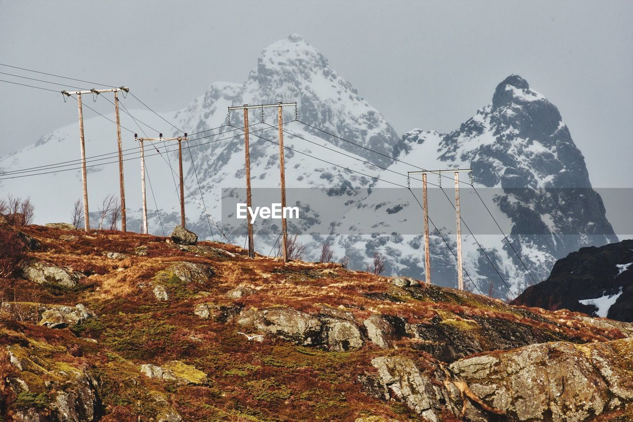 Low Angle View Of Electricity Pylon Against Snowcapped Mountains On Sunny Day