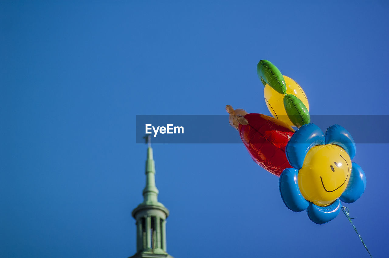 blue, sky, clear sky, no people, representation, nature, low angle view, copy space, multi colored, animal representation, art and craft, balloon, creativity, sunlight, built structure, architecture, craft, day, outdoors, bird, inflatable
