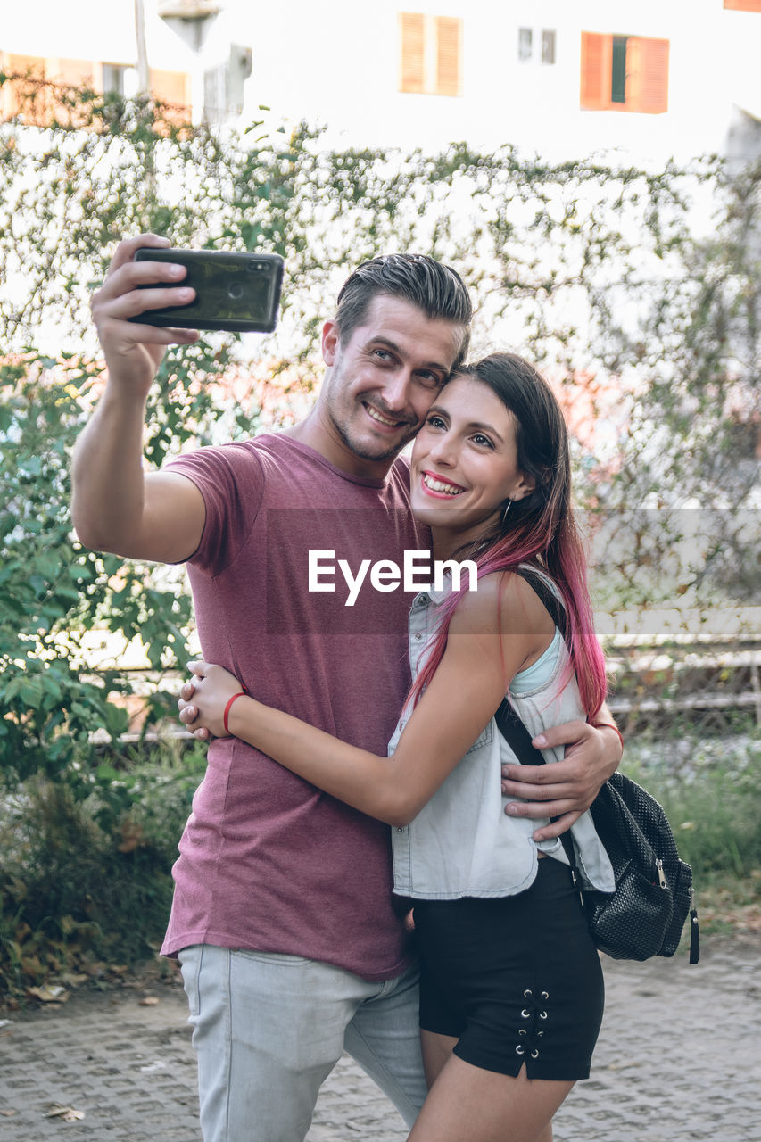 A portrait of brunette young couple smiling and taking selfie photo while walking outdoors