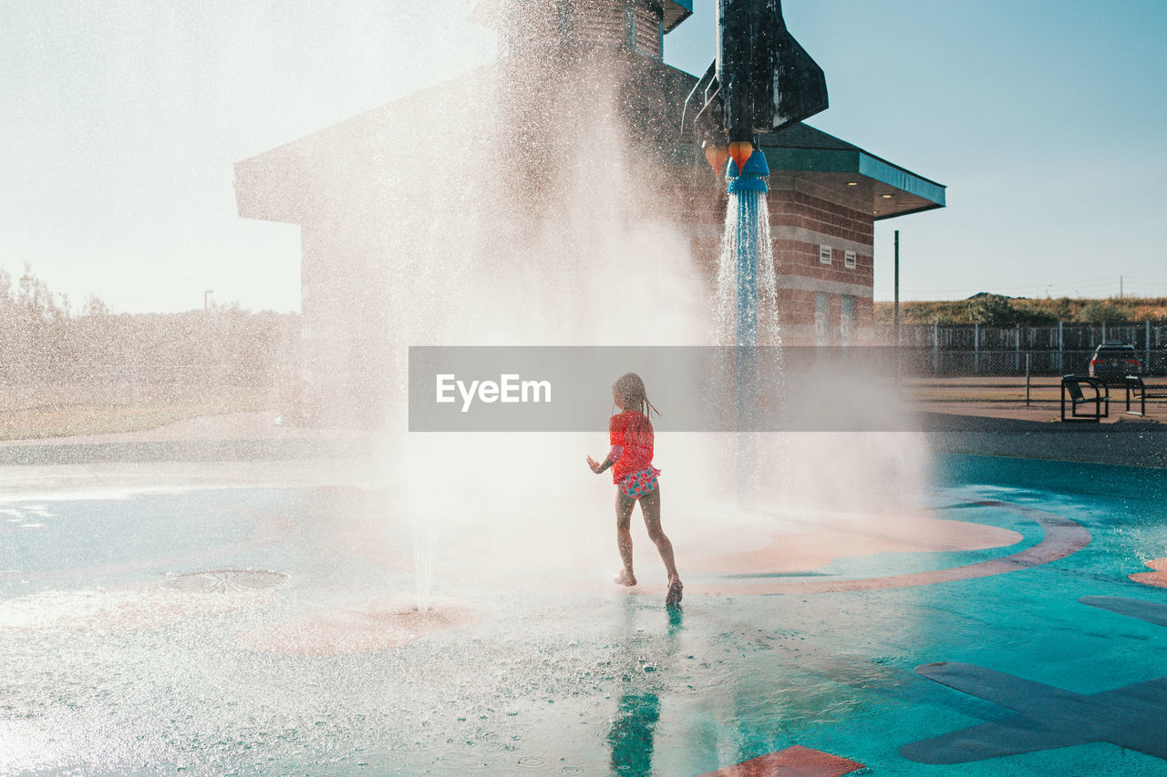 Cute adorable caucasian funny girl playing on splash pad playground on summer day.