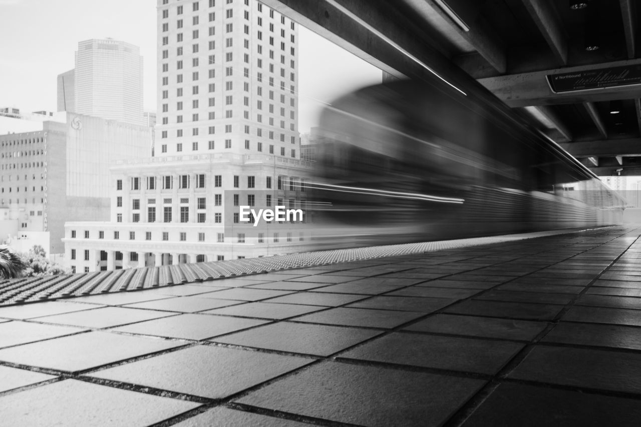 architecture, blurred motion, built structure, city, building exterior, motion, transportation, public transportation, mode of transportation, rail transportation, building, no people, train, speed, street, office building exterior, travel, outdoors, city life, long exposure, modern, tiled floor, skyscraper