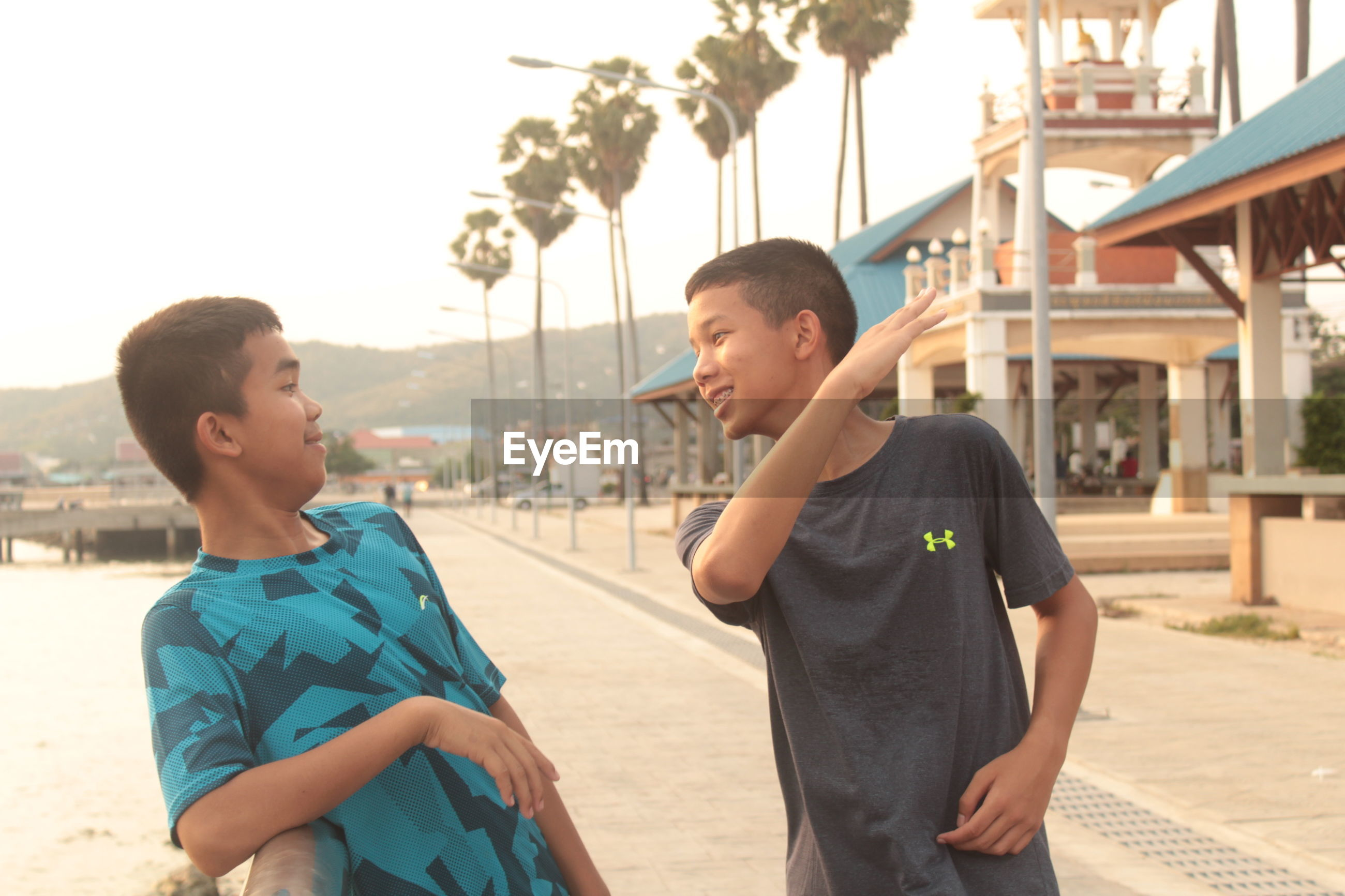 Boy gesturing to friend while standing at pier against sky