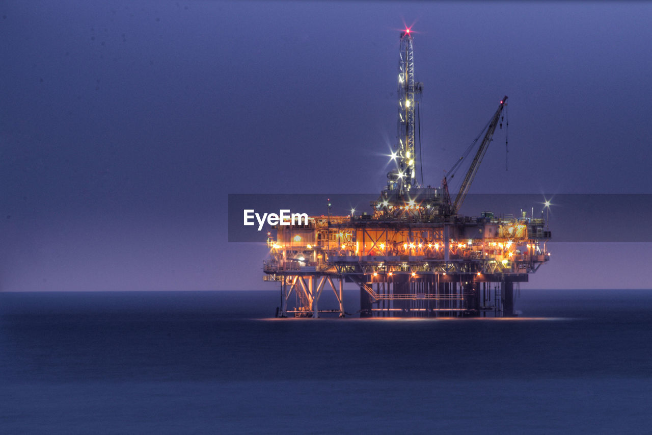 Illuminated drilling rig in sea against clear sky at night