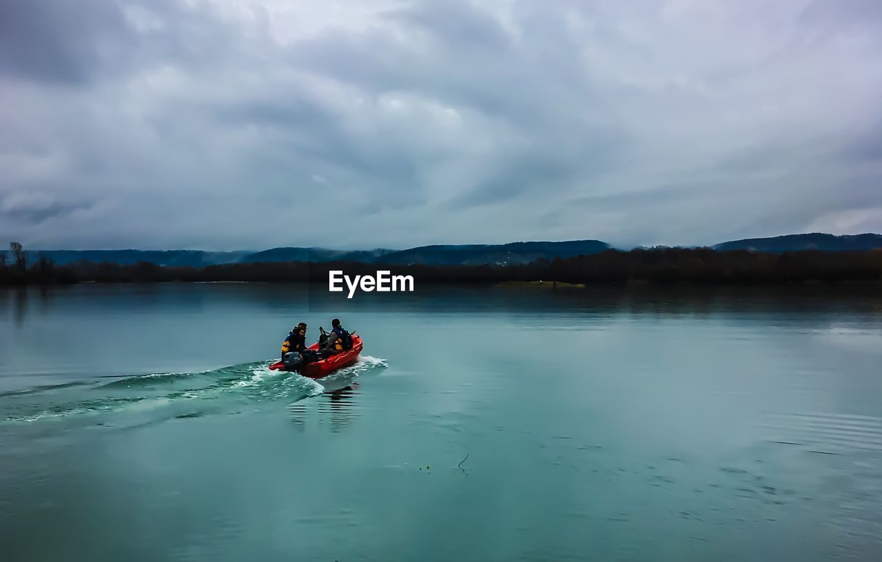 People sitting in boat on river against cloudy sky