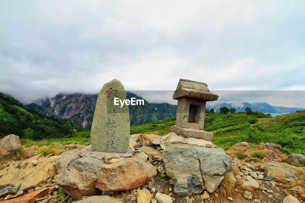 Stones on mountain against cloudy sky