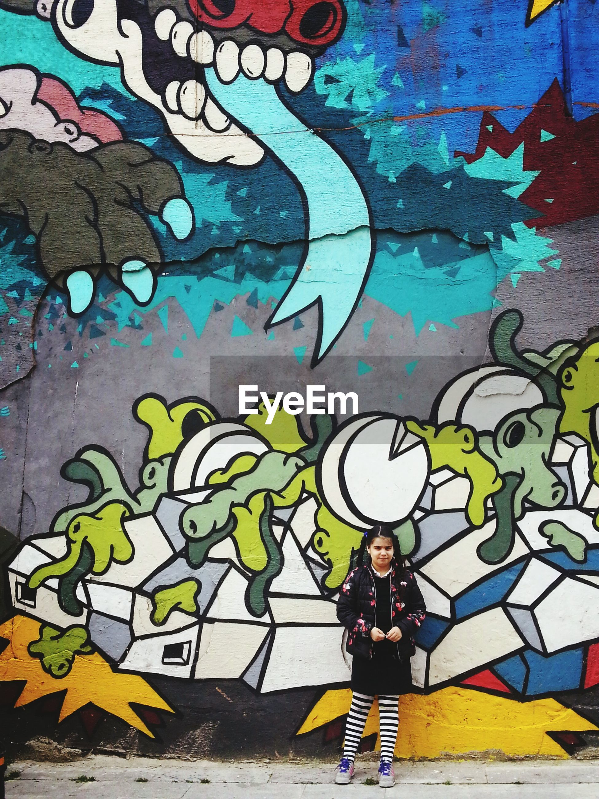 graffiti, lifestyles, wall - building feature, leisure activity, art, multi colored, creativity, art and craft, casual clothing, standing, built structure, architecture, full length, childhood, wall, men, boys, street art