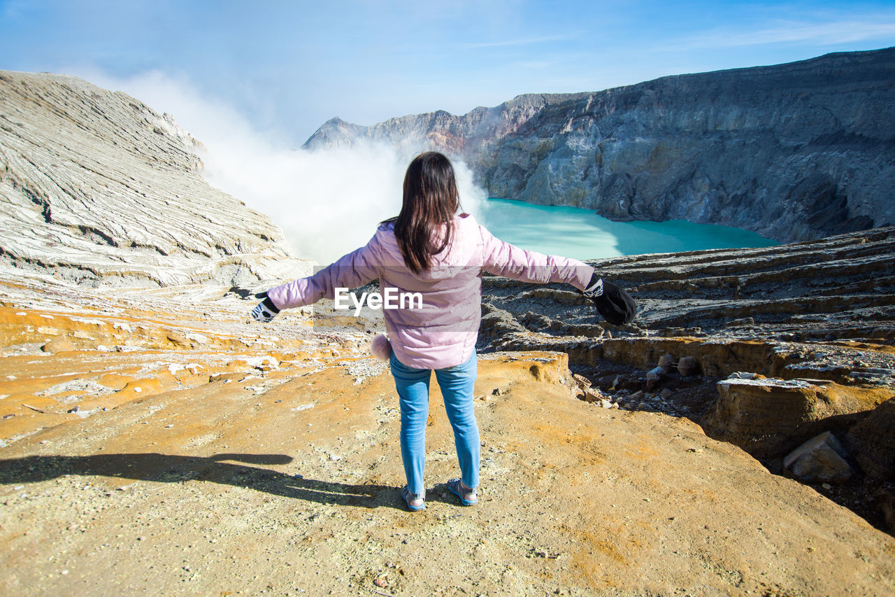 Rear View Of Woman With Arms Outstretched Standing On Rock