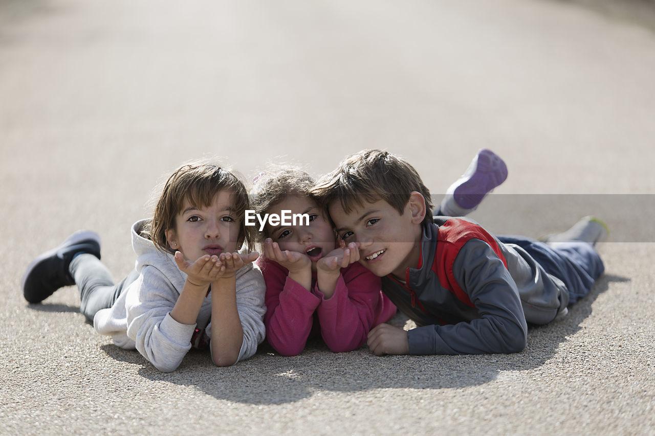 Portrait Of Siblings Lying Down On Road