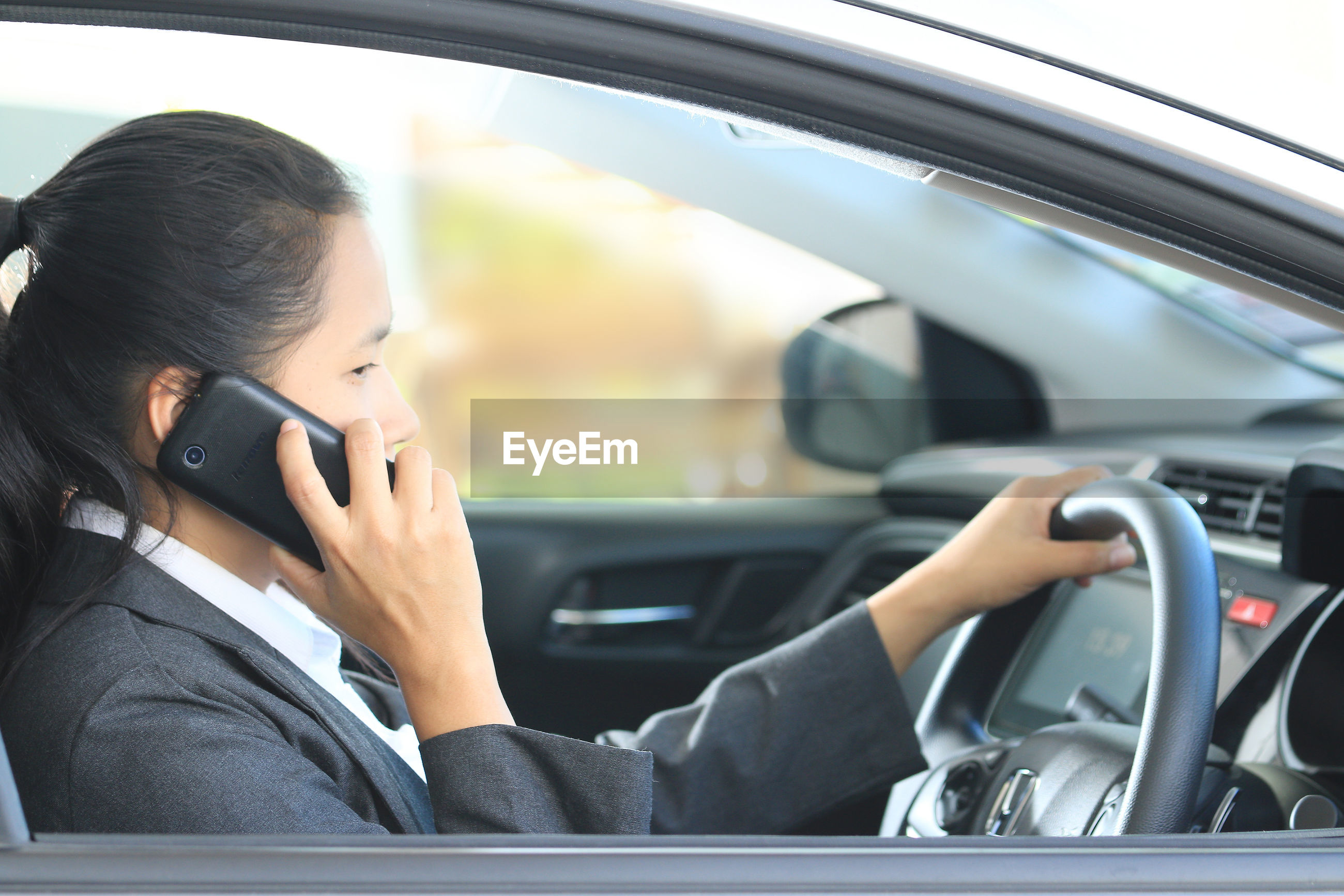 Businesswoman using mobile phone while driving car