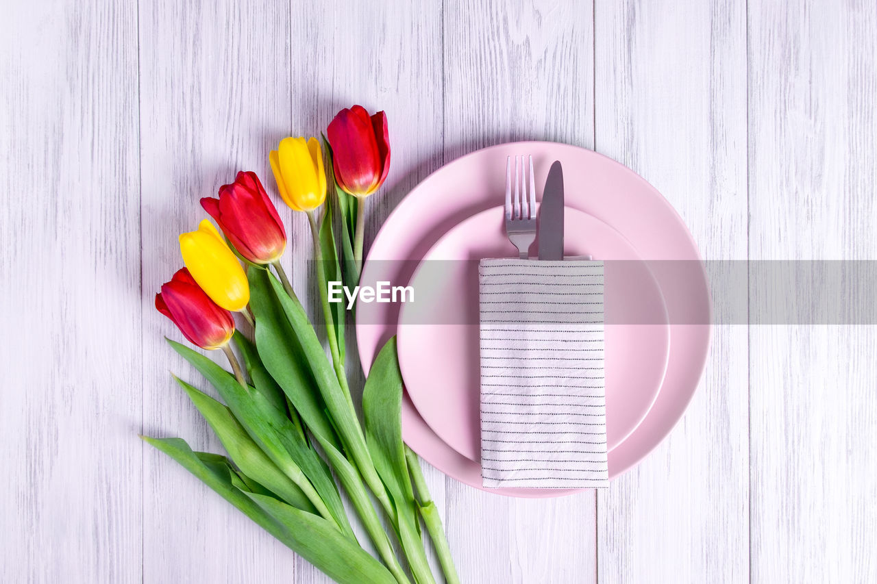 DIRECTLY ABOVE SHOT OF MULTI COLORED TULIPS ON WOODEN TABLE