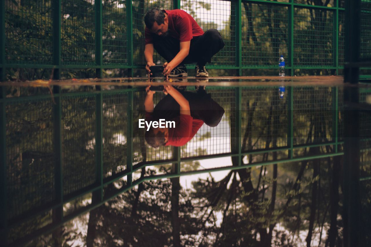 Man Photographing Puddle Through Mobile Phone While Crouching By Fence
