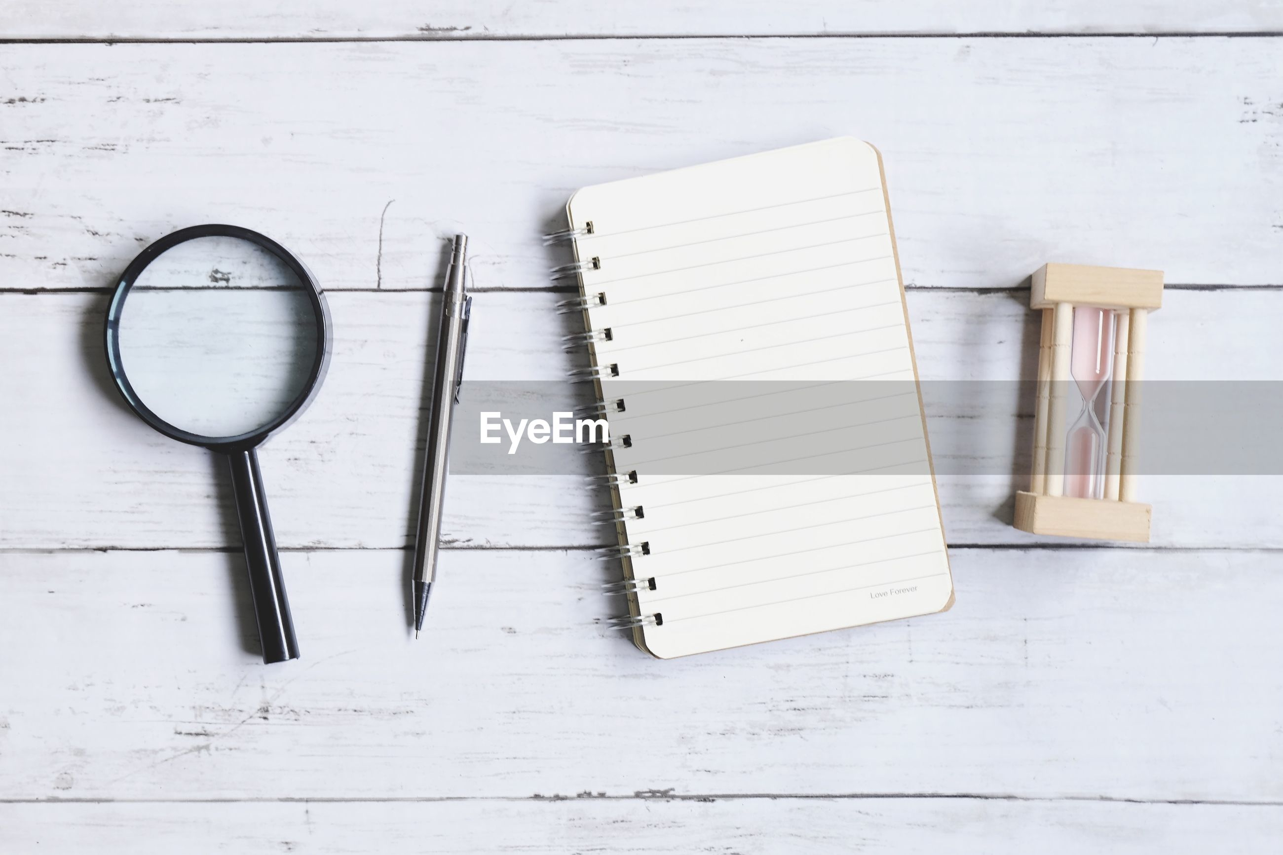 Directly above shot of spiral notebook with pen and hourglass on wooden table